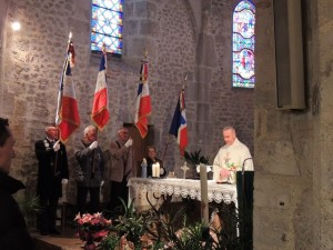 L'aumônier officie à l'autel, les porte-drapeaux de chaque côté