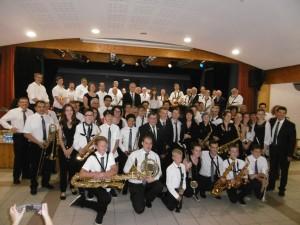 Les musiciens de La Lyre Agenaise et leur Chef devant debout sur la scène et devant au sol les musiciens de La fleurantine et leur directeur musical Vincent Blesz, tout à fait à droite sur la photo.