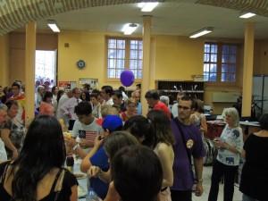 Les gens se retrouvent devant les tables bien achalandées en victuailles et boissons