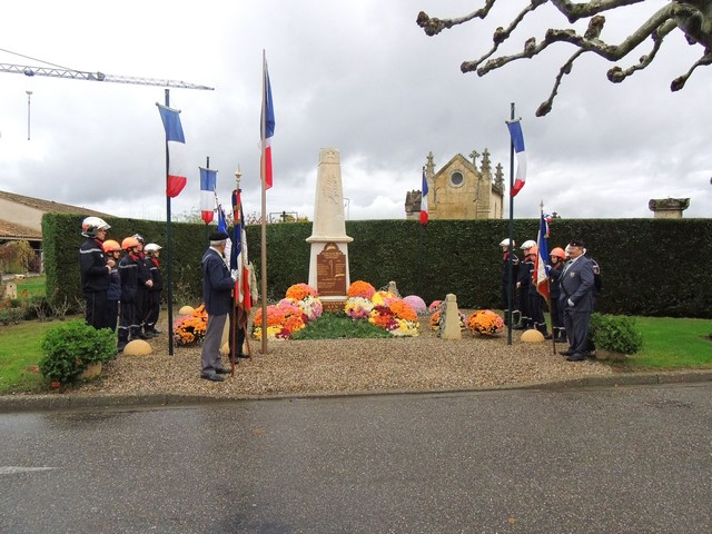 Les pompiers et les porte-drapeaux de part et d'autre du monument aux Morts à Brax