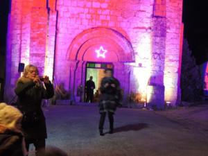Les musiciens font une aubade sur la Place devant le parvis fortifié illuminé et l'entrée de l'église