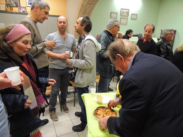 Jean-Claude tend une part de galette à Adrienne, pendant que Thierry, Alain et Frédéric discutent.