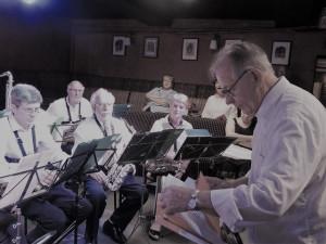 Les musiciens sont attentifs aux directives du Chef qui met ses partitions en place sur son pupitre ; Le concert de l'harmonie va commencer...!
