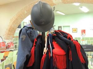 Des tenues complètes suspendues et à côté une tenue de tambour et son casque