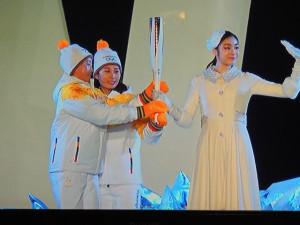 Elles tiennent ensemble la flamme pour la transmettre à la coupole olympique