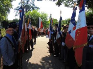 A l'entrée du parc  la haie des porte-drapeaux; tout au fond la statue sous son voile tricolore