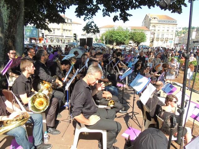 Les musiciens au premier plan et derrière l'assistance nombreuse suivent la cérémonie